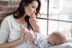 亲吻一个新出生的婴孩的脚的愉快的母亲 免版税库存照片