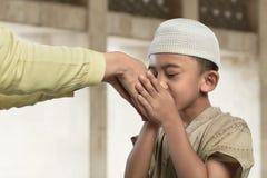 亲吻从一位老人的亚裔回教孩子一只手 库存图片