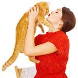 亲吻一只红色猫的美丽的深色的女孩 免版税库存照片