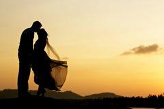 亲吻与日落的婚礼夫妇 免版税库存照片