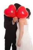 亲吻与红色心脏轻快优雅的新娘对被隔绝在白色 免版税库存照片