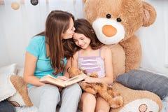 亲吻两个逗人喜爱的微笑的姐妹读和 库存照片