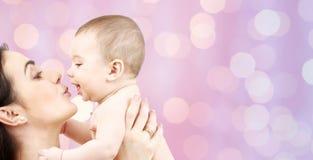 亲吻可爱的婴孩的愉快的母亲 库存图片