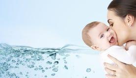 亲吻可爱的婴孩的愉快的母亲 免版税库存照片