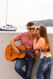 亲吻年轻吉他弹奏者的女孩 免版税库存照片