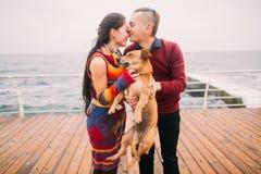 亲吻和使用与在多雨停泊处的狗的年轻愉快的夫妇在秋天 背景峡湾光芒海运星期日 免版税库存图片