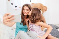 亲吻和做selfie的两个俏丽的微笑的姐妹 免版税库存照片