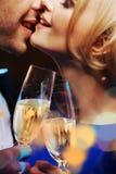 亲吻和喝香槟的年轻夫妇 库存图片