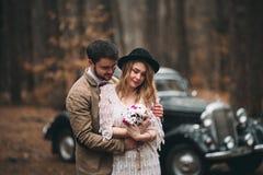 亲吻和拥抱在杉木森林里的浪漫童话婚礼夫妇在减速火箭的汽车附近 免版税图库摄影