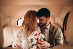 亲吻和拥抱在杉木森林里的浪漫童话婚礼夫妇在减速火箭的汽车附近 图库摄影