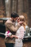 亲吻和拥抱在杉木森林里的浪漫童话婚礼夫妇在减速火箭的汽车附近 免版税库存图片
