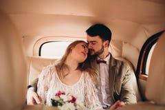 亲吻和拥抱在杉木森林里的浪漫童话婚礼夫妇在减速火箭的汽车附近 库存图片
