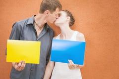 亲吻和拿着框架背景的年轻夫妇 免版税库存照片