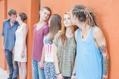 亲吻和站立在红色墙壁背景附近的中等小组ofpeople 图库摄影