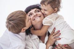 亲吻哄骗男孩和女孩的妇女微笑的母亲 免版税库存图片