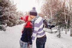 亲吻在一个日期的爱恋的夫妇在一个冬天停放 在人背面垂悬一双冰鞋 免版税库存照片