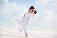 亲吻在一个热带海滩的新娘和新郎 免版税库存照片