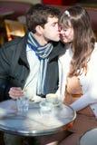 亲吻在一个巴黎人咖啡馆的夫妇 免版税图库摄影