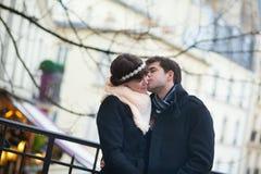 亲吻在一条巴黎人街道上的夫妇 免版税库存图片