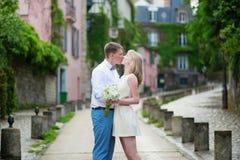 亲吻在一条巴黎人街道上的新娘和新郎 库存图片