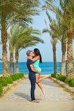 亲吻在与棕榈树的海滩的浪漫夫妇 免版税库存图片