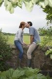 亲吻在乡下墙壁上的夫妇 免版税库存照片