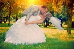亲吻在公园的婚礼夫妇在日落instagram窗框 图库摄影