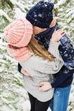 亲吻在冷杉木中的多雪的森林里的逗人喜爱的夫妇 免版税图库摄影