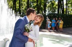 亲吻在喷泉附近的新郎和新娘 免版税库存照片