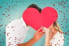 亲吻在夸大的心后的有吸引力的年轻夫妇的综合图象 库存照片
