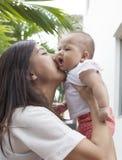 亲吻在她的母性和婴儿的婴孩面颊用途的母亲我 免版税库存照片
