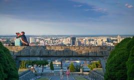 亲吻在布拉索夫战争纪念建筑SlavÃn地平线,全景前面的夫妇 免版税库存照片