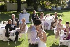 亲吻在庭院里的新娘和新郎 免版税库存图片