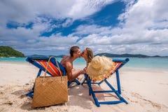 亲吻在懒人的热带海滩的夫妇 图库摄影