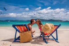亲吻在懒人的热带海滩的夫妇 免版税库存图片