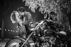 亲吻在摩托车背后的夫妇在晚上 免版税库存图片