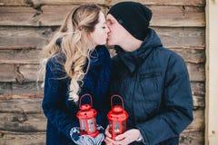 亲吻在木背景的愉快的夫妇在降雪下 库存照片
