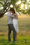 亲吻在树下的夫妇 免版税库存图片
