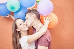亲吻在橙色墙壁附近的年轻愉快的夫妇站立与气球 免版税图库摄影