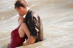 亲吻在海的男人和妇女 免版税库存图片
