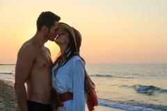 亲吻在海滩的愉快的年轻夫妇在黄昏 免版税库存照片