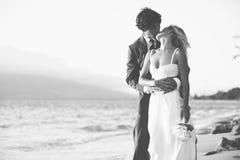 亲吻在海滩的新娘和新郎 免版税图库摄影