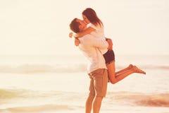 亲吻在海滩的浪漫夫妇在日落 免版税库存照片