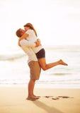 亲吻在海滩的浪漫夫妇在日落 免版税库存图片