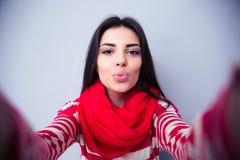 亲吻在灰色背景的照相机的美丽的妇女 免版税库存照片