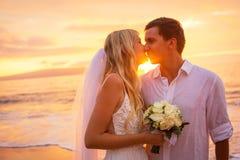 亲吻在热带海滩的已婚夫妇在日落 免版税库存图片