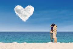 亲吻在爱云彩下的夫妇在海滩 免版税库存照片