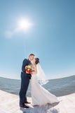亲吻在码头的年轻婚礼夫妇 库存图片