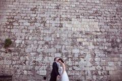 亲吻在砖墙附近的新郎和新娘 免版税库存图片