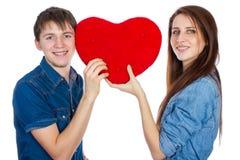 亲吻在红色心脏后的美好的年轻愉快的夫妇,举行它在手上,隔绝在白色背景 库存照片